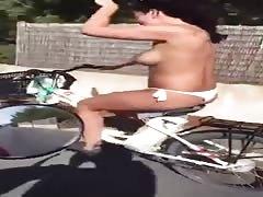 Chica en topless monta en bici por Formentera